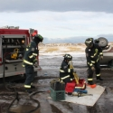 Firefighters prepare extrication equipment.